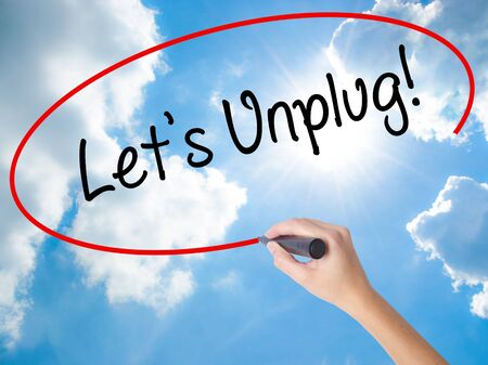 Woman Hand Writing Lets Unplug! with black marker on visual screen. Isolated on Sunny Sky. Business concept. Stock Photo