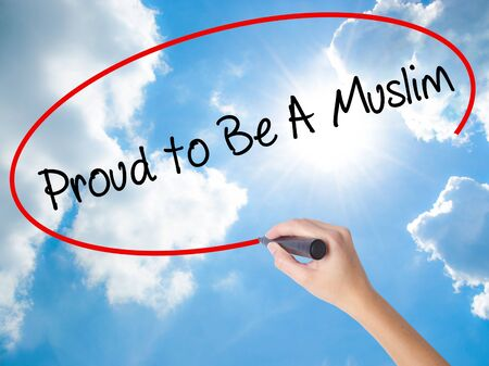 algeria: Woman Hand Writing Proud to Be A Muslim with black marker on visual screen. Isolated on Sunny Sky. Business concept. Stock Photo