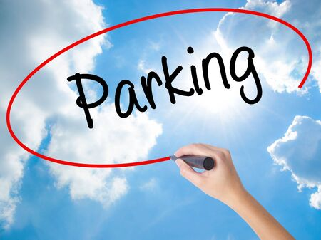 storey: Woman Hand Writing Parking with black marker on visual screen. Isolated on Sunny Sky. Business concept. Stock Photo