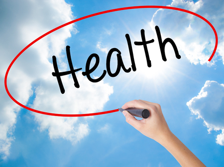 Woman Hand Writing Health with black marker on visual screen. Isolated on Sunny Sky. Business concept. Stock Photo