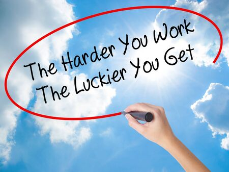 Woman Hand Writing The Harder You Work The Luckier You Get  with black marker on visual screen. Isolated on Sunny Sky. Business, technology, internet concept.