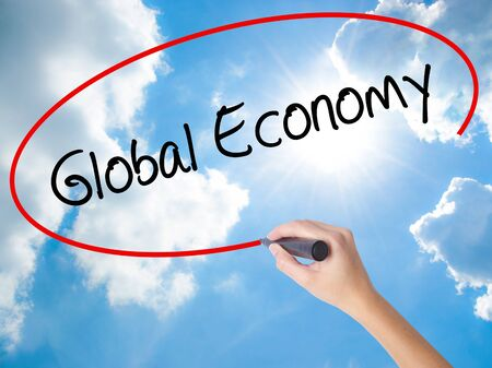 Woman Hand Writing Global Economy with black marker on visual screen. Isolated on Sunny Sky. Business concept. Stock Photo