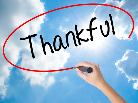 obliged: Woman Hand Writing Thankful  with black marker on visual screen. Isolated on Sunny Sky. Business concept. Stock Photo