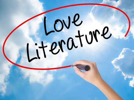 Woman Hand Writing Love Literature with black marker on visual screen. Isolated on Sunny Sky. Business concept. Stock Photo Stock Photo