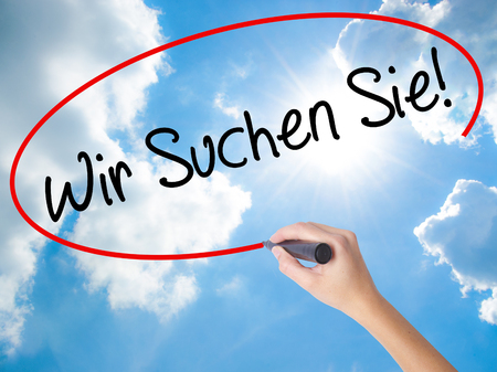 Woman Hand Writing Wir Suchen Sie! (Looking For You in German) with black marker on visual screen. Isolated on Sunny Sky. Business,  technology, internet concept. Stock Photo
