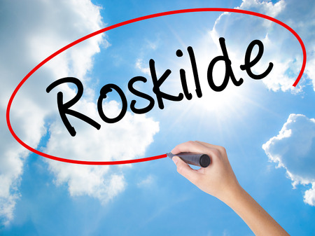 humanismo: Woman Hand Writing Roskilde  with black marker on visual screen. Isolated on Sunny Sky. Business concept. Stock Photo