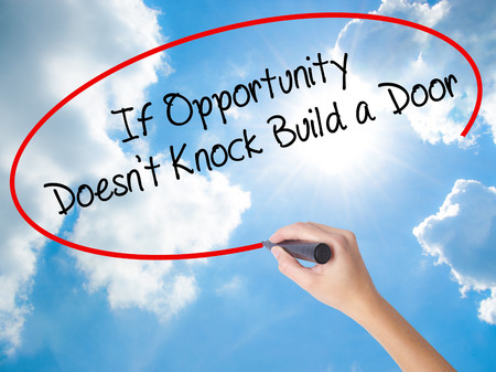 tocar la puerta: Woman Hand Writing If Opportunity Doesnt Knock Build a Door with black marker on visual screen. Isolated on Sunny Sky. Business concept. Stock Photo