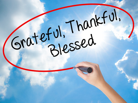 humility: Woman Hand Writing  Grateful Thankful Blessed with black marker on visual screen. Isolated on Sunny Sky. Business concept. Stock Photo