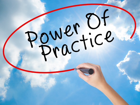 Woman Hand Writing Power Of Practice with black marker on visual screen. Isolated on Sunny Sky. Business concept. Stock Photo