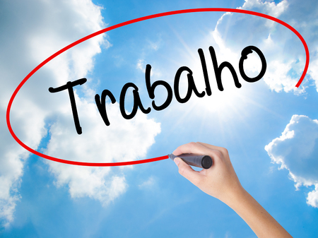 Woman Hand Writing Trabalho (Work in Portuguese) with black marker on visual screen. Isolated on Sunny Sky. Business concept. Stock Photo