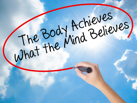 Woman Hand Writing The Body Achieves What the Mind Believes with black marker on visual screen. Isolated on Sunny Sky. Business concept. Stock Photo