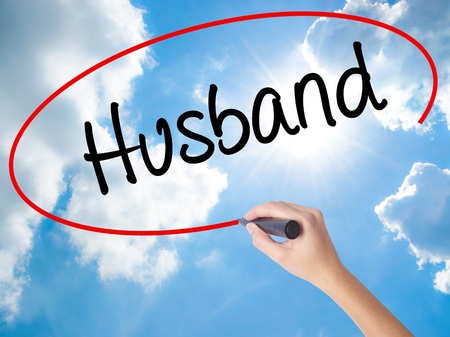 Woman Hand Writing Husband with black marker on visual screen. Isolated on Sunny Sky. Business concept. Stock Photo