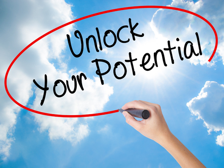 Woman Hand Writing Unlock Your Potential with black marker on visual screen. Isolated on Sunny Sky. Business concept. Stock Photo
