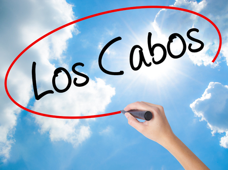 Woman Hand Writing Los Cabos with black marker on visual screen. Isolated on Sunny Sky. Business concept. Stock Photo