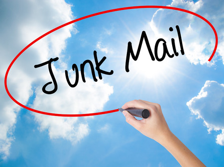 solicitors: Woman Hand Writing Junk Mail with black marker on visual screen. Isolated on Sunny Sky. Business concept. Stock Photo
