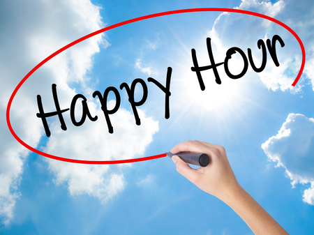 happyhour: Woman Hand Writing Happy Hour with black marker on visual screen. Isolated on Sunny Sky. Business concept. Stock Photo