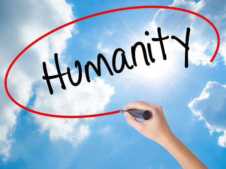 Woman Hand Writing Humanity  with black marker on visual screen. Isolated on Sunny Sky. Business concept. Stock Photo