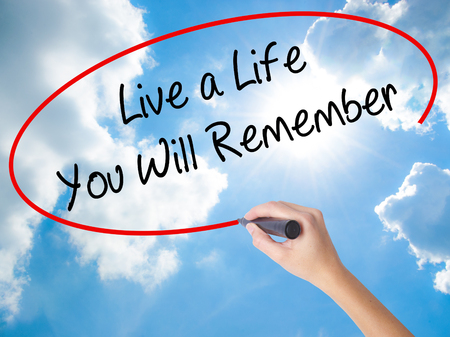 bonne aventure: Woman Hand Writing Live a Life You Will Remember with black marker on visual screen. Isolated on Sunny Sky. Business, technology, internet concept.
