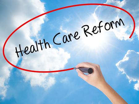 Woman Hand Writing Health Care Reform with black marker on visual screen. Isolated on Sunny Sky. Business, technology, internet concept.