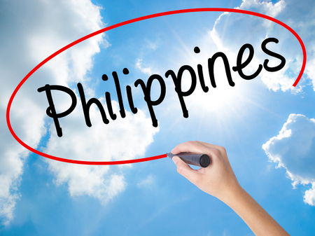 Woman Hand Writing Philippines with black marker on visual screen. Isolated on Sunny Sky. Business concept. Stock Photo Stock Photo
