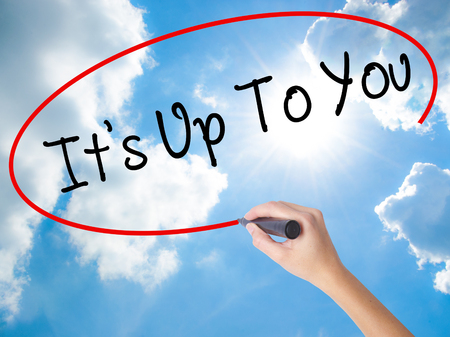 Woman Hand Writing Its Up To You with black marker on visual screen. Isolated on Sunny Sky. Business concept. Stock Photo