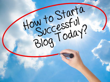 Woman Hand Writing How to Start a Successful Blog Today? with black marker on visual screen. Isolated on Sunny Sky. Business concept. Stock Photo Stock Photo