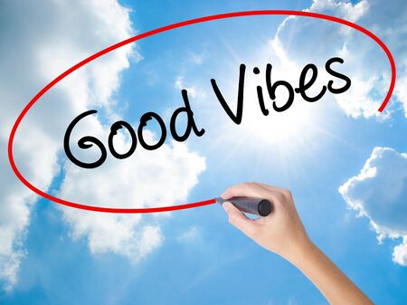 Woman Hand Writing Good Vibes with black marker on visual screen. Isolated on Sunny Sky. Business concept. Stock Photo Stock Photo
