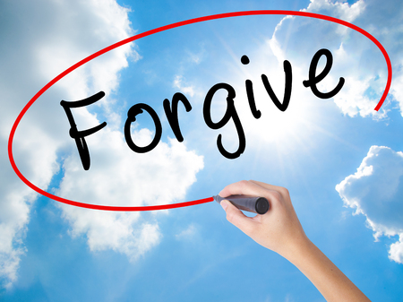 délivrance: Woman Hand Writing Forgive with black marker on visual screen. Isolated on Sunny Sky. Business concept. Stock Photo