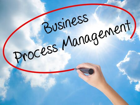 Woman Hand Writing Business Process Management with black marker on visual screen. Isolated on Sunny Sky. Business concept. Stock Photo