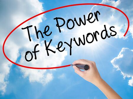 Woman Hand Writing The Power of Keywords with black marker on visual screen. Isolated on Sunny Sky. Business concept. Stock Photo