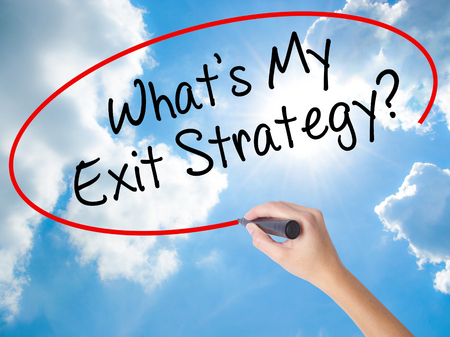 Woman Hand Writing Whats My Exit Strategy? with black marker on visual screen. Isolated on Sunny Sky. Business concept. Stock Photo Stock Photo