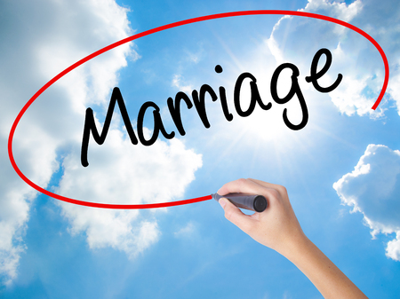 Woman Hand Writing Marriage with black marker on visual screen. Isolated on Sunny Sky. Business concept. Stock Photo
