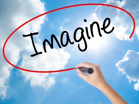 Woman Hand Writing Imagine  with black marker on visual screen. Isolated on Sunny Sky. Business concept. Stock Photo Stock Photo