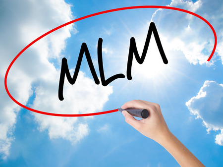 Woman Hand Writing  MLM (Multi-Level Marketing) with black marker on visual screen. Isolated on Sunny Sky. Business concept. Stock Photo