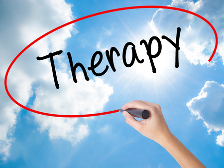 Woman Hand Writing Therapy  with black marker on visual screen. Isolated on Sunny Sky. Business concept. Stock Photo Stock Photo