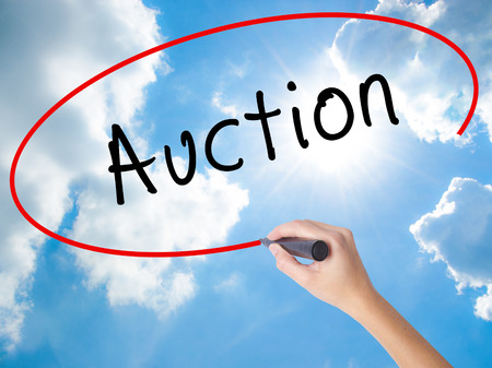 technology transaction: Woman Hand Writing Auction with black marker on visual screen. Isolated on Sunny Sky. Business concept. Stock Photo