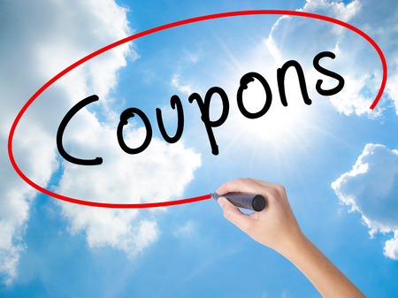 Woman Hand Writing Coupons black marker on visual screen. Isolated on Sunny Sky. Business concept. Stock Photo