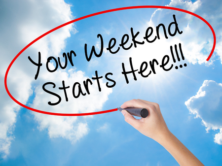 Woman Hand Writing Your Weekend Starts Here!!! with black marker on visual screen. Isolated on Sunny Sky. Business concept. Stock Photo