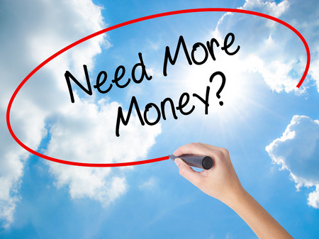Woman Hand Writing Need More Money? with black marker on visual screen. Isolated on Sunny Sky. Business concept. Stock Photo