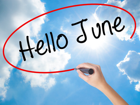 Woman Hand Writing Hello June  with black marker on visual screen. Isolated on Sunny Sky. Business concept. Stock Photo