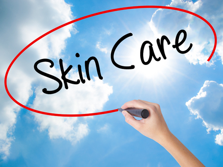 Woman Hand Writing Skin Care with black marker on visual screen. Isolated on Sunny Sky. Business concept. Stock Photo