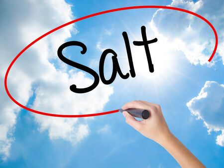 Woman Hand Writing Salt with black marker on visual screen. Isolated on Sunny Sky. Business concept. Stock Photo Stock Photo
