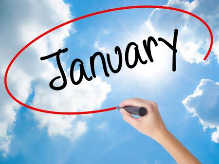 Woman Hand Writing January with black marker on visual screen. Isolated on Sunny Sky. Business concept. Stock Photo