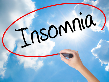 Woman Hand Writing Insomnia  with black marker on visual screen. Isolated on Sunny Sky. Business concept. Stock Photo Stock Photo