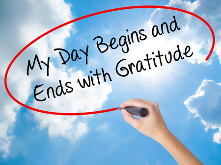 humility: Woman Hand Writing My Day Begins and Ends with Gratitude with black marker on visual screen. Isolated on Sunny Sky. Business concept. Stock Photo Stock Photo