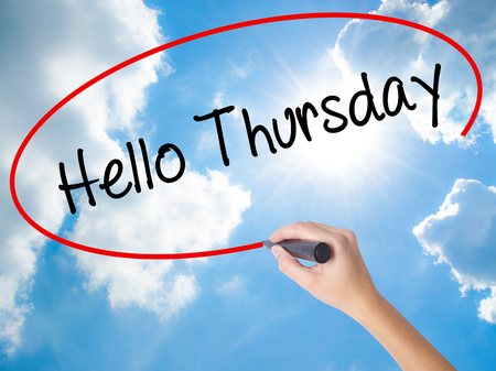 Woman Hand Writing Hello Thursday with black marker on visual screen. Isolated on Sunny Sky. Business concept. Stock Photo