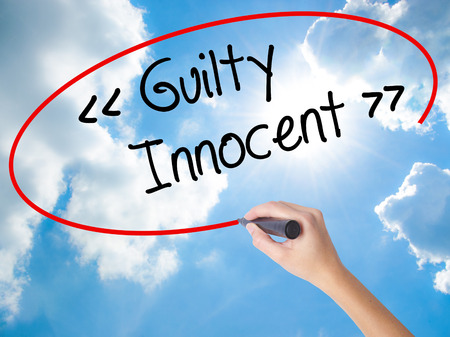 Woman Hand Writing Guilty - Innocent with black marker on visual screen. Isolated on Sunny Sky. Business concept. Stock Photo