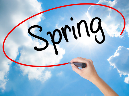 eastertime: Woman Hand Writing Spring with black marker on visual screen. Isolated on Sunny Sky. Business concept. Stock Photo