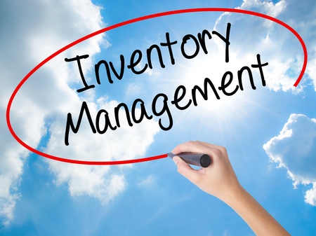 Woman Hand Writing Inventory Management with black marker on visual screen. Isolated on Sunny Sky. Business concept. Stock Photo