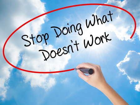 Woman Hand Writing Stop Doing What Doesnt Work with black marker on visual screen. Isolated on Sunny Sky. Business concept. Stock Photo Stock Photo